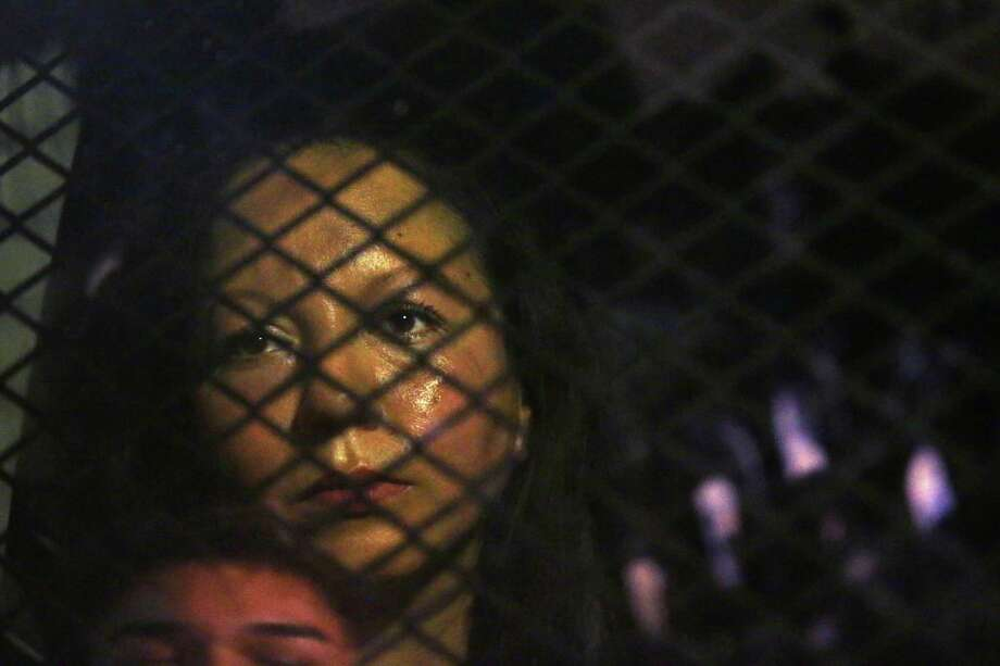 Guadalupe Garcia de Rayos is locked in a van that is stopped in the street by protesters outside the Immigration and Customs Enforcement facility Wednesday, Feb. 8, 2017, in Phoenix. Apparently fearing her deportation, activists blocked the gates surrounding the office near central Phoenix in what the Arizona Republic says was an effort to block several vans and a bus inside from leaving. (Rob Schumacher/The Arizona Republic via AP) ORG XMIT: AZPHP201 Photo: Rob Schumacher / The Arizona Republic