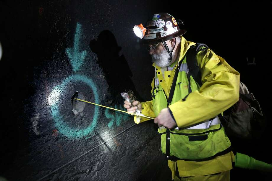 Project engineer  Glenn Boyce measures the depth of the Mountain Tunnel wall through a drilled core sample hole. Photo: Michael Macor, The Chronicle