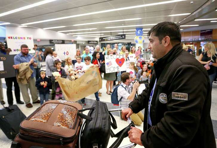 Noor, who came to the United States from Afghanistan under a Special Immigrant visa with his wife and seven children, is greeted by well-wishers and resettlement workers at Bush IAH on. Thursday