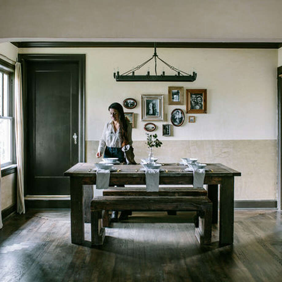 """The dining room of the Portland home that Eva Kosmas Flores shares with her husband, Jeremy Flores, is full of character. Here and in the living room, Eva applied two tones of split plaster on the walls, which adds dimension and warmth against the dark decor. Eva, who runs the popular blog Adventures in Cooking, also created a gallery wall of old family photographs. """"Family has been the single reason behind why I'm so passionate about food,"""" she says.Restoration plaster; masterofplaster.com. Paint tint in Casa Blanca and Windsor Greige; sherwin-williams.com. Camino vintage filament round chandelier, from $895; restorationhardware.com. Photo: Eva Kosmas Flores"""