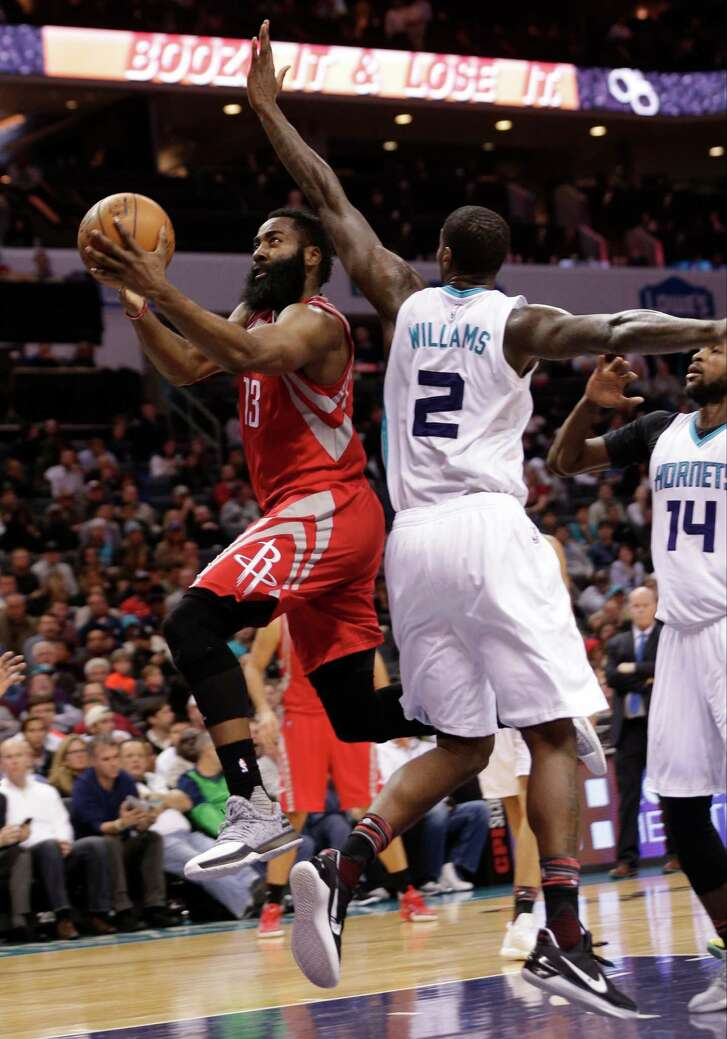 The Rockets' James Harden, left, drives past the Hornets' Marvin Williams for two of his game-high 30 points. It was his 14th 30-point game in 25 outings.