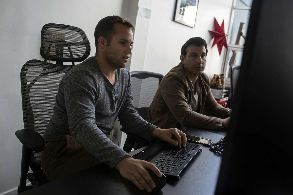 Founder Jason Stomel, left, and Serj Amir, right, discuss client relationships at the recruiting firm Cadre Talent on February 9, 2017, in Los Angeles, Calif. Stomel says that although they have not been directly affected by U.S. President Donald Trump's executive order blocking visitors from seven predominantly Muslim nations but that companies they work with are acting cautious.