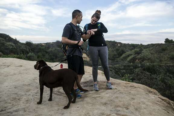 Kevin and Crystal Mo-Wong check their fitness activity on their Fitbit's while hiking the Fullerton Loop hiking trail on February 9, 2017 in Fullerton, Calif. The couple says their Fitbit's have added a layer to the relationship, encouraging them to work out together and talk about their daily activity.