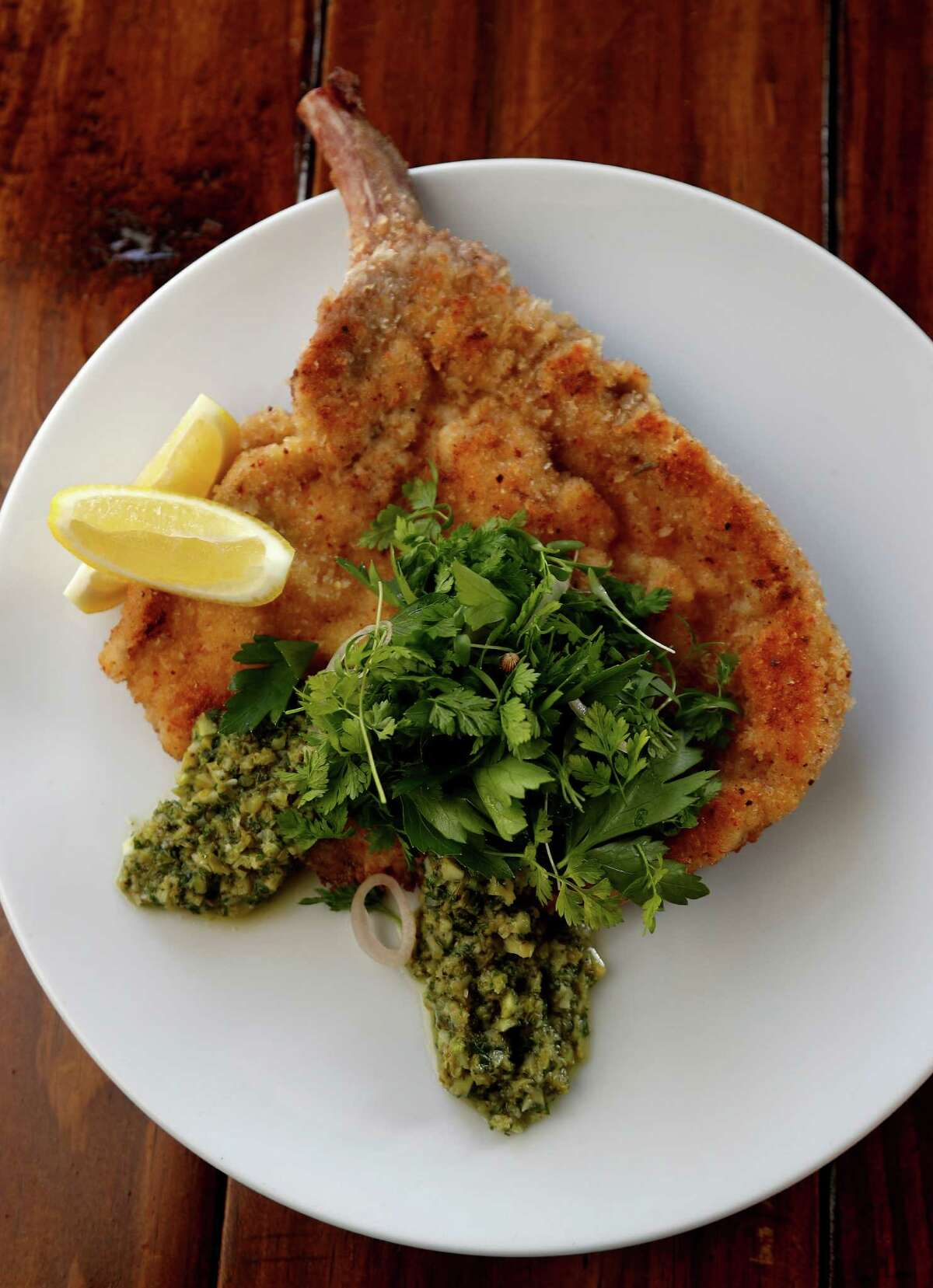 Pastured Pork Milanese, heirloom polenta, preserved lemon, broccoli, and salsa verde at Presidio 911 W. 11th St., in the Heights.