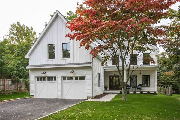 The newly constructed modern colonial farmhouse at 219 Lovers Lane has white James Hardie brand maintenance-free board siding and signature black trim around windows.