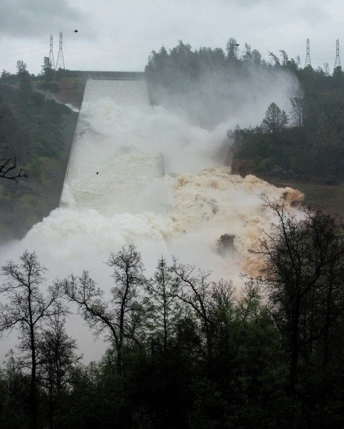 The California Department of Water Resources and host of collaborating agencies continue to monitor the Lake Oroville spillway flows late Thursday afternoon as 35,000 cubic feet per second (cfs) of water was released over the damaged spillway. More erosion is expected, but the releases will help operators absorb the inflow of the storm waters expected Thursday evening and Friday. DWR first noticed erosion on the spillway Tuesday morning and shut off flows to investigate. There is no imminent or expected threat to public safety or the integrity of Oroville Dam in Butte County. Photo taken 3:10 p.m. PST February 9, 2017. Kelly M. Grow/ California Department of Water Resources