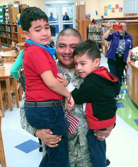 U.S. Air Force Technical Sgt. Jesus Garza, who has been serving overseas, shares a moment with his two children, Jesus Emiliano, 8, and Jesus Alejandro, 3, at their school Thursday. Garza had not seen his children since last summer and surprised them in the Ryan Elementary library, where students also thanked him for his service in the military. According to Laredo ISD, Garza had been stationed in Turkey. Photo: Cuate Santos /Laredo Morning Times / Laredo Morning Times
