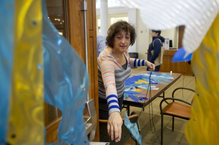 "Artist Elena Kalman of Stamford works on a portion of ""The Wave,"" a public art installation project that was briefly on display at the Ferguson Library in Stamford in 2014. The project was inspired by water. Kalman created it along with fellow artist Susan Hoffman Fishman. Photo: Lindsay Perry / File Photo / Stamford Advocate"