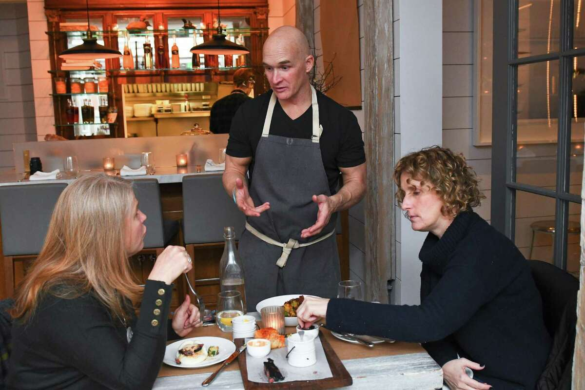 Chef Brian Lewis at his restaurant, The Cottage in Westport, talks with Westport residents and regulars Katherine Bruan, right, and Melanie Tribe about their meal.