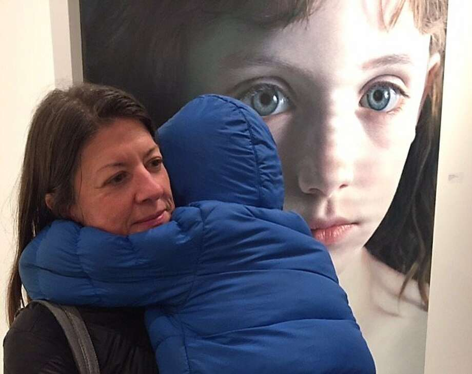 Dinene Himes and son Emmett in front of Gottfried Helnwein painting �at Modernism Gallery Photo: Leah Garchik, San Francisco Chronicle