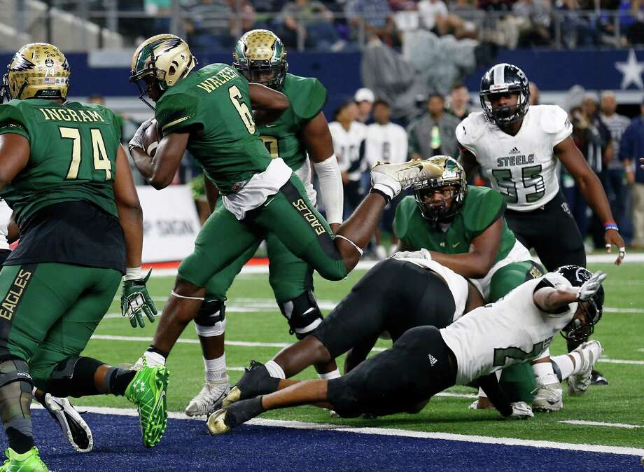 DeSoto's Kelan Walker leaps over Steele defenders for a touchdown in the Class 6A Division II state championship football game at AT&T Stadium in Arlington on Saturday, Dec. 17, 2016. Photo: Kin Man Hui, San Antonio Express-News / ©2016 San Antonio Express-News