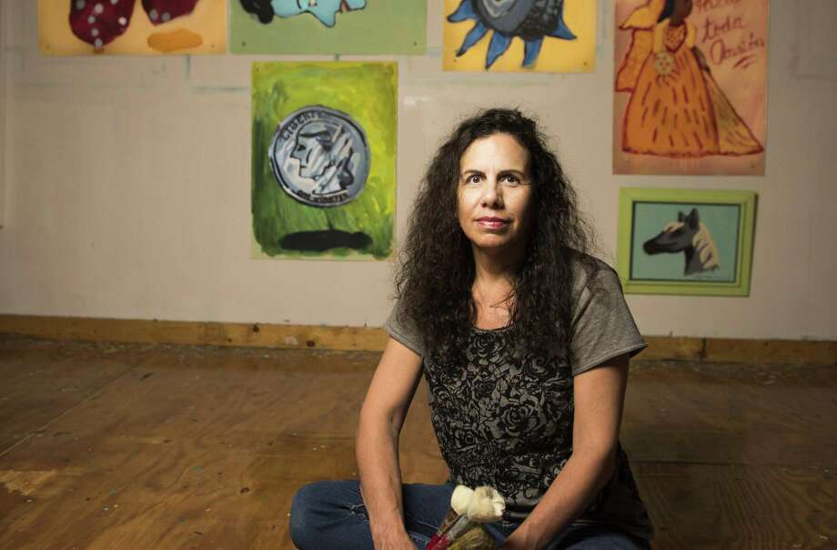 Artist Victoria Suescum has reinterpreted the traditional symbols of the tarot with icons derived from hand-painted signs created as advertising for mom and pop shops. The pieces behind her are arranged in the same configuration as the cards Suescum drew in a recent reading. Photo: Carlos Javier Sanchez / For The Express News / / pixelreflex.com