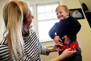Ashley Perkin, of Fairfield, dresses her son Scott, 3, in a Gell belt, in their home in the Southport section of Fairfield, Conn. on Wednesday, February 8, 2017. Perkin and husband Richard started Gell Belts two years ago and now sell adult and kids lines from their website www.gells.org as well as through local boutiques.