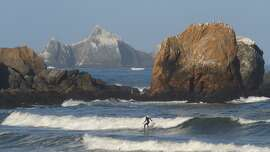 A surfer glides past a rocky point near Pacifica State Beach with San Pedro Rock looming in the background. Surfing was named the official sport of California this week, even though the sport originated in Hawaii.