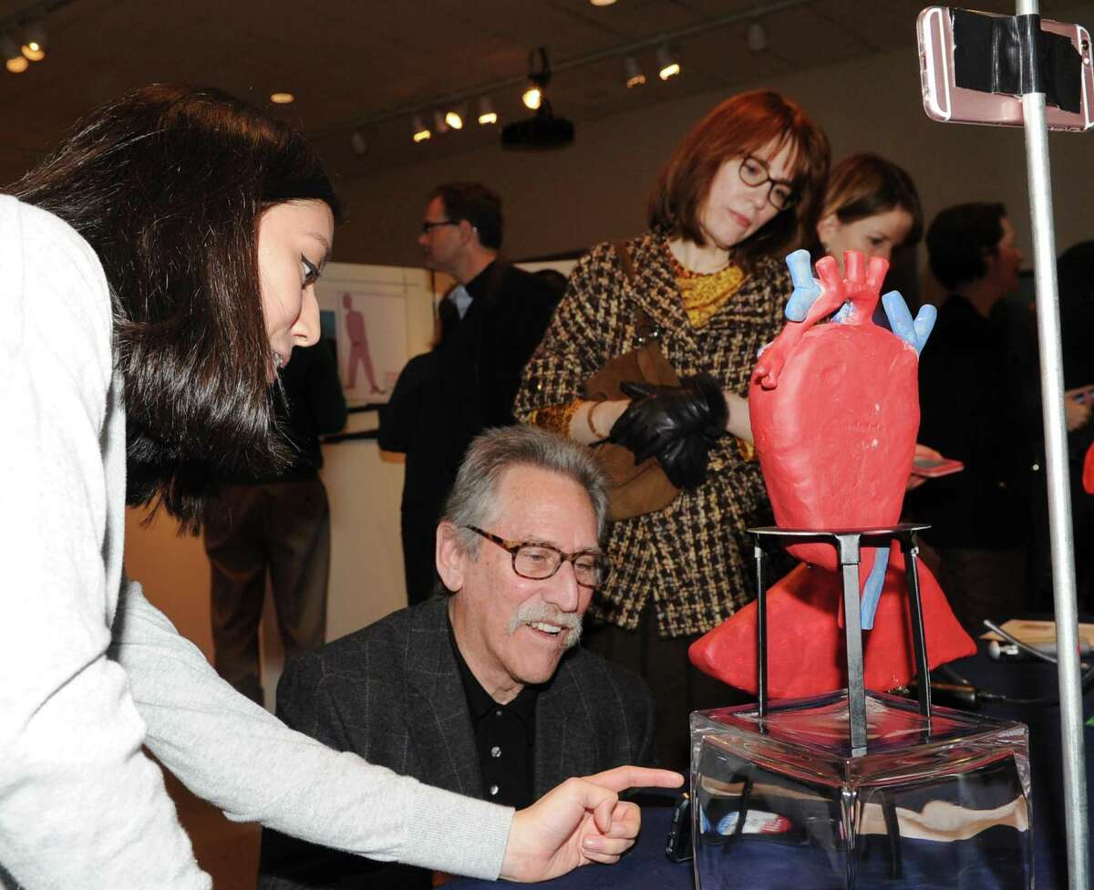 """Greenwich High School sophomore Alexandra Cid, 15, left, explains her """"The Beast of Obesity"""" project to Warren Bratter of Cos Cob during the Innovation Lab program exhibition at the Bruce Museum in Greenwich, Conn., Wednesday night, Feb. 8, 2017."""