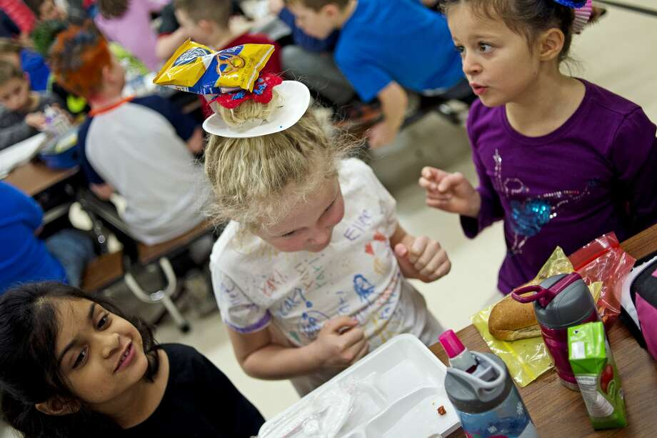 From left, Adams Elementary first-grader Tanisha Hasan, 6, gazes off as first grader Ellee Arnold, 7, balances pretzels on her donut hairdo which were put on her head by first grader Sera Dimulo, 7, right, during Wacky Hair Day on Friday at Adams Elementary. Kids wore their hair in various colors, styles and shapes as part of Adams Spirit Days. The next Spirit Day will be on Mar. 17, and the theme is Pure Michigan Day. Photo: Erin Kirkland/Midland Daily News/Erin Kirkland