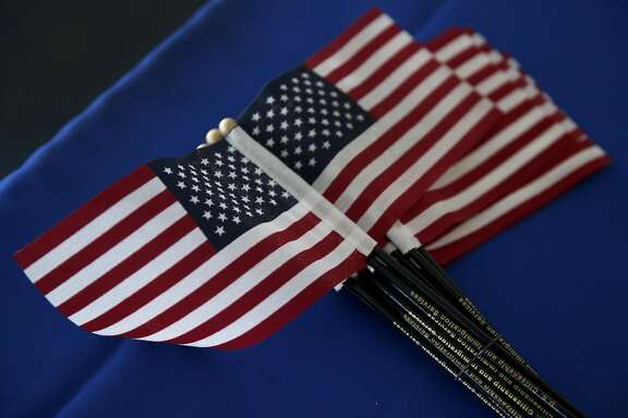 American flags are handed out to the 22 new U.S. citizens that took the Oath of Allegiance at a naturalization ceremony in Hayward, Calif. on Friday, Dec. 11, 2015.
