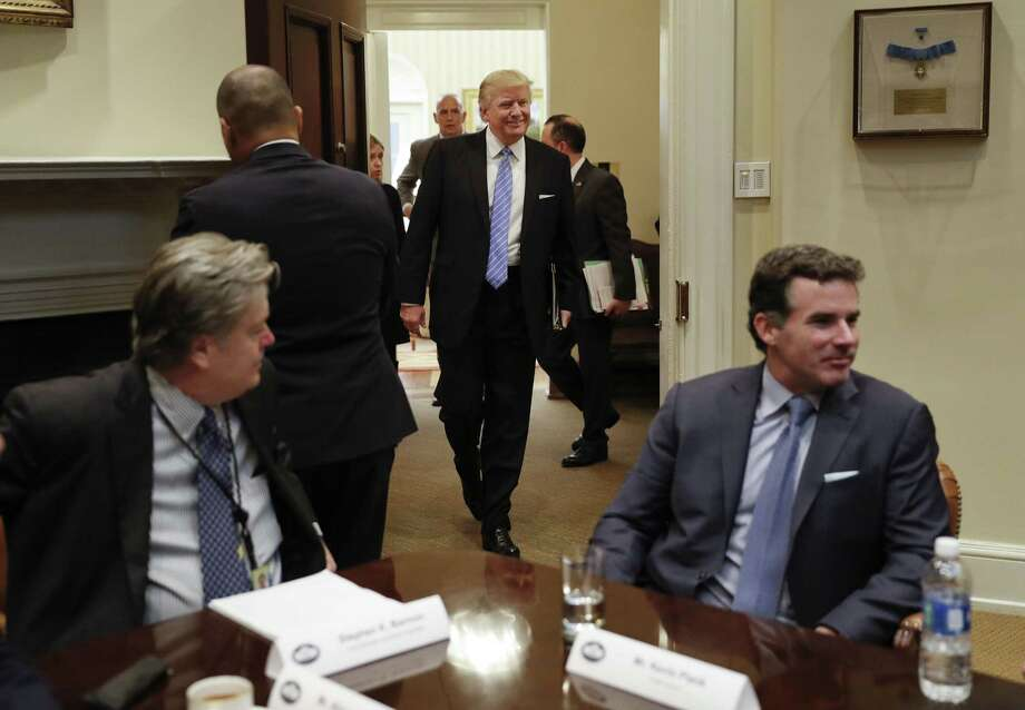 """President Donald Trump walks in from the Oval Office to host a Jan. 23 breakfast with business leaders in the Roosevelt Room. Sitting at the table are White House senior adviser Steve Bannon (left) and Kevin Plank, founder, CEO and chairman of Under Armour. Plank has said Trump is a """"real asset for the country."""" Photo: Pablo Martinez Monsivais /Associated Press / Copyright 2017 The Associated Press. All rights reserved."""