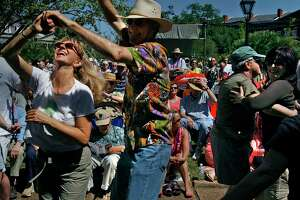 Richard and Alana Eager enjoy the music and sun as the French Quarter Festival opens in the New Orleans Jackson Square.