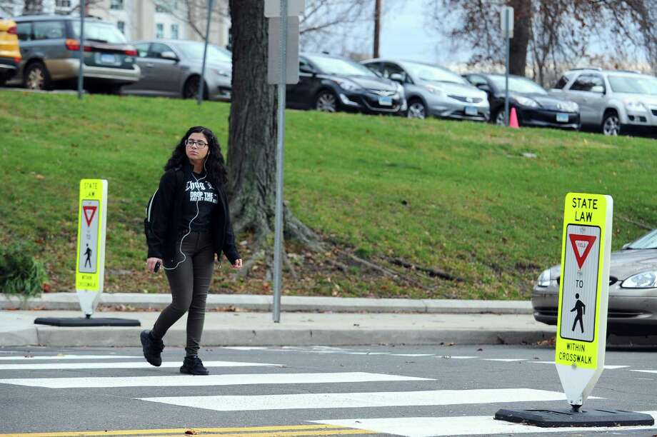 A Stamford High School student looks to see if traffic will yield while crossing the street outside of her school in Stamford, Conn. on Thursday, Dec. 1, 2016. Photo: Michael Cummo / Hearst Connecticut Media / Stamford Advocate