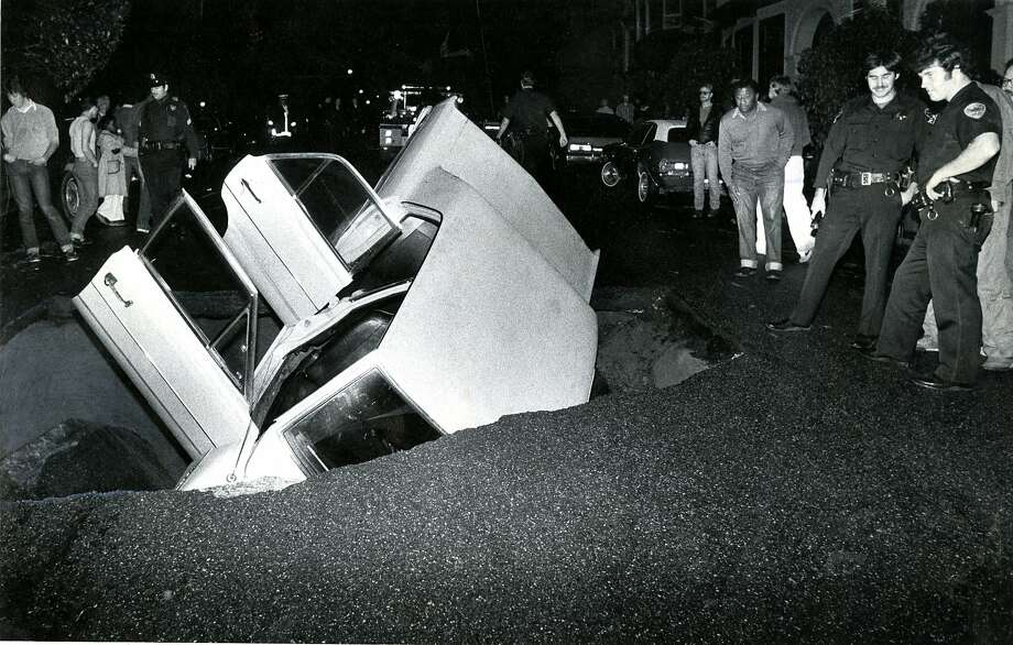 November 16, 1981:  Car being swallowed up in a sinkhole at Central and Oak Streets in San Francisco. Photo: Susan Gilbert, San Francisco Chronicle