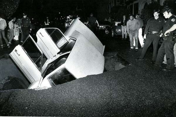November 16, 1981:  Car being swallowed up in a sinkhole at Central and Oak Streets in San Francisco.