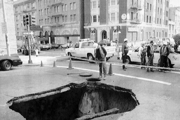 December 14, 1990: A worker from the San Francisco Department of Public Works peers into the collapsed portion of Jones Street at Bush Street intersection. The cause of the cave in, approximately 24 feet around and ten feet deep, was under investigation. Photo courtesy of the AP.