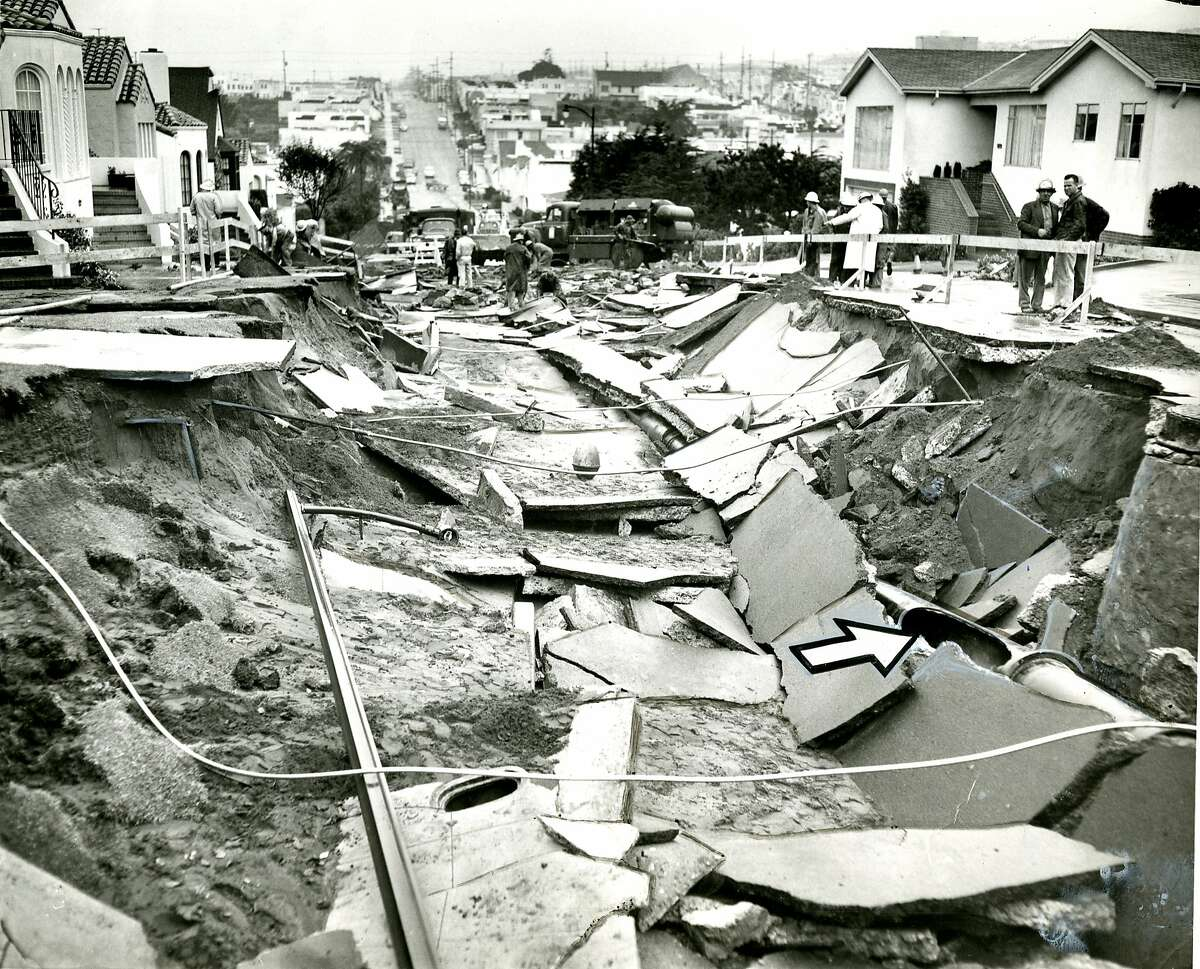 December 1, 1960: Vast sinkhole appeared along the 2700 block of 34th Avenue in San Francisco. the arrow points to a broken sewer line.