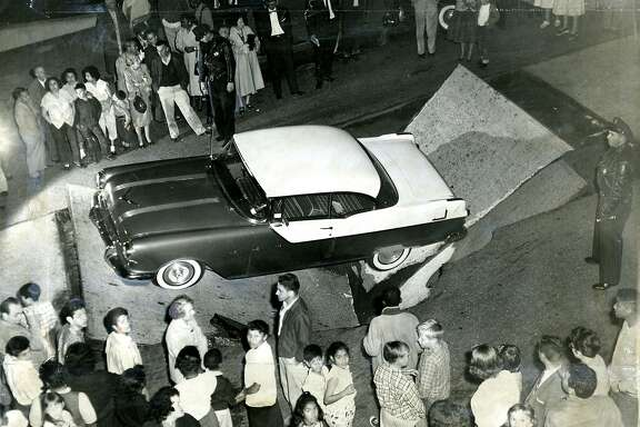 November 27,  1957: A cave in trapped an auto. A San Francisco mother and her two children were driving south on Central Avenue, between Turk Street and Golden Gate Avenue, when a section of pavement collapsed. Arnetta Scott and her two young children were taken to Park Emergency Hospital. They were released when it was determined that they were uninjured. It took two  tow trucks half an hour to remove the auto from the hold. The collapse was caused by a leaking sewer.