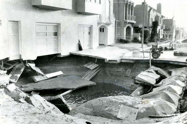 "July 25, 1981: A broken water main caused a 25' diameter hole, 10' deep. A sign, ""Open for inspection"" fell into the hole, on Judah Street in San Francisco's Sunset District."