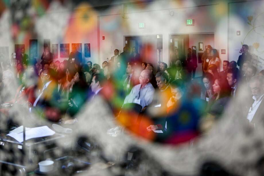 Attendees at a Greenlining Institute luncheon last week are seen reflected in an art piece. Photo: Amy Osborne, Special To The Chronicle