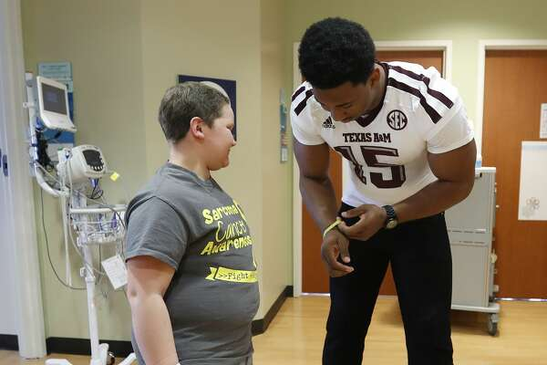 "Myles Garrett puts twelve-year-old Damon Billeck's ""TeamDamon support wrist band on his wrist  during his visit to MD Anderson, Friday, February 10, 2017. Garrett, a DE from Texas A&M is projected as the overall No.1 draft pick in the upcoming NFL draft.  ( Karen Warren / Houston Chronicle )"