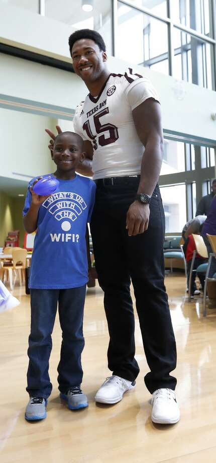 Myles Garrett makes bunny ears behind Trey Thomas, 8,  at MD Anderson, Friday, February 10, 2017. Garrett, a DE from Texas A&M is projected as the overall No.1 draft pick in the upcoming NFL draft.  ( Karen Warren / Houston Chronicle ) Photo: Karen Warren/Houston Chronicle