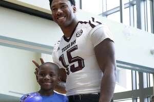 Myles Garrett makes bunny ears behind Trey Thomas, 8,  at MD Anderson, Friday, February 10, 2017. Garrett, a DE from Texas A&M is projected as the overall No.1 draft pick in the upcoming NFL draft.  ( Karen Warren / Houston Chronicle )