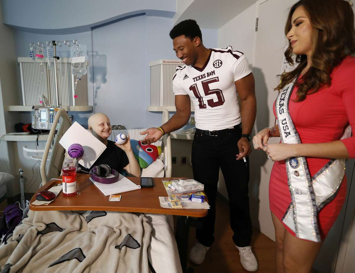 Myles Garrett gives Courtney Fink, 16, a football with Miss Texas, Nancy Gonzalez at Texas Children's, Friday, February 10, 2017. Garrett, a DE from Texas A&M is projected as the overall No.1 draft pick in the upcoming NFL draft. ( Karen Warren / Houston Chronicle )