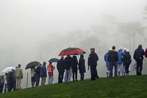 Spectators stand along the ninth green of the Spyglass Hill Golf Course and wait for the start of the delayed second round of the AT&T Pebble Beach National Pro-Am golf tournament Friday, Feb. 10, 2017, in Pebble Beach, Calif. (AP Photo/Eric Risberg)