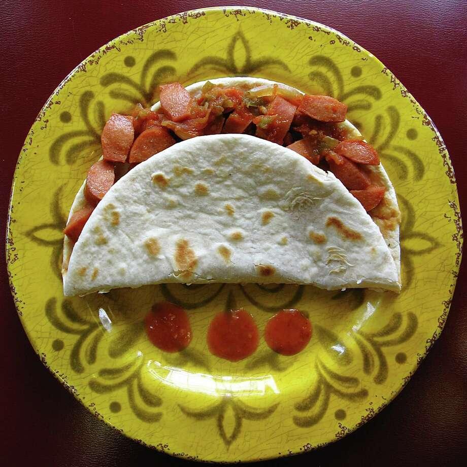 A weenies rancheras taco on a handmade flour tortilla from La Esquinita. Photo: Mike Sutter /San Antonio Express-News