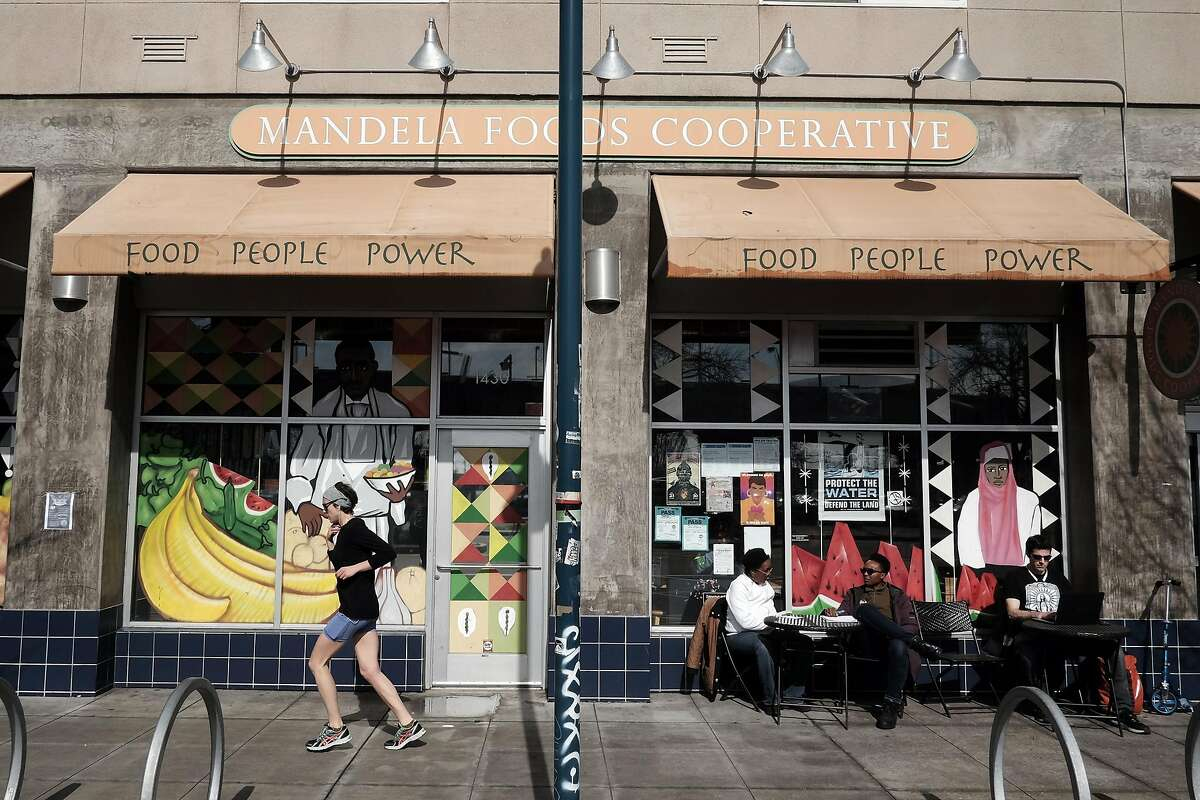 People sit at tables outside Mandela Foods Co-op in West Oakland.