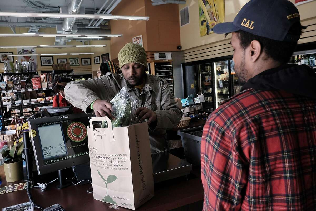 Worker/owner James Bell bags up groceries for customer Bernard Bailey at Mandela Foods Co-op in Oakland.