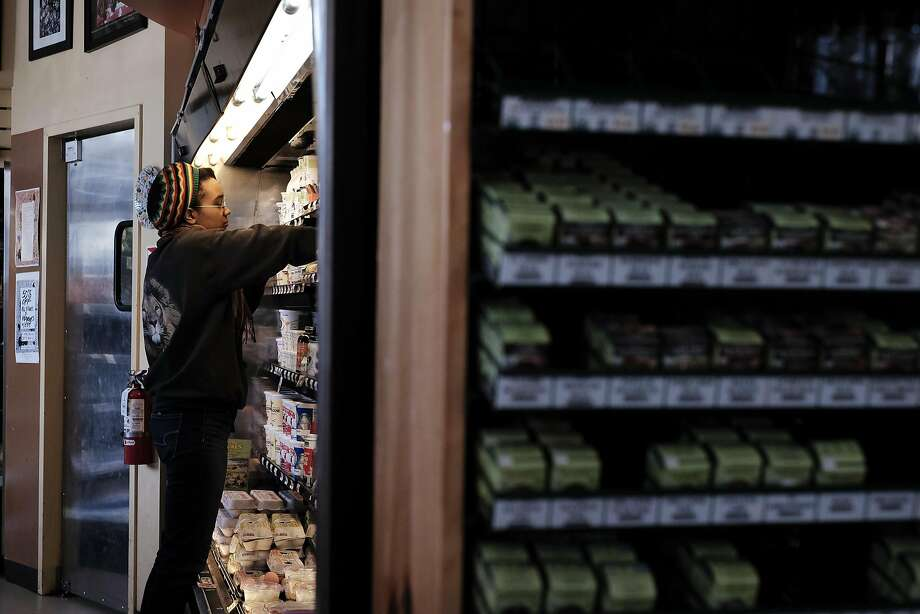 Worker Erin Clark stocks the dairy case at Mandela Foods Cooperative in Oakland. Photo: Michael Short, Special To The Chronicle