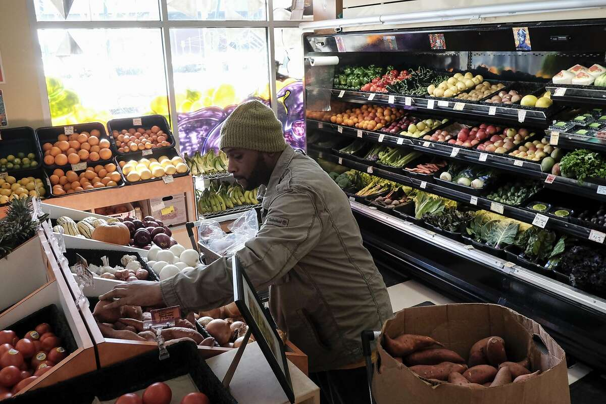 Worker/owner James Bell stocks sweet potatoes in the produce section Mandela Foods Co-op in Oakland, CA on Friday, February 10, 2017.