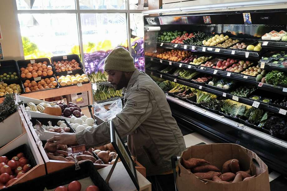 Worker-owner James Bell stocks sweet potatoes in the produce section at Mandela Foods Cooperative in Oakland. Photo: Michael Short, Special To The Chronicle