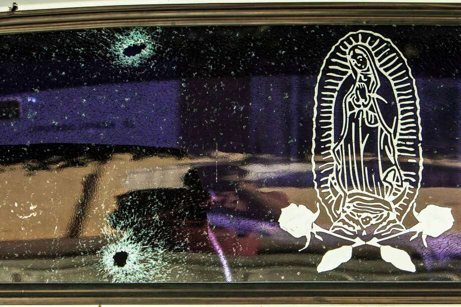 A car's rear windshield is held together by a film with an image of the Virgin of Guadalupe, after being struck during gunfire involving Mexican marines.  Photo: Rashide Frias, STR / Copyright 2017 The Associated Press. All rights reserved.
