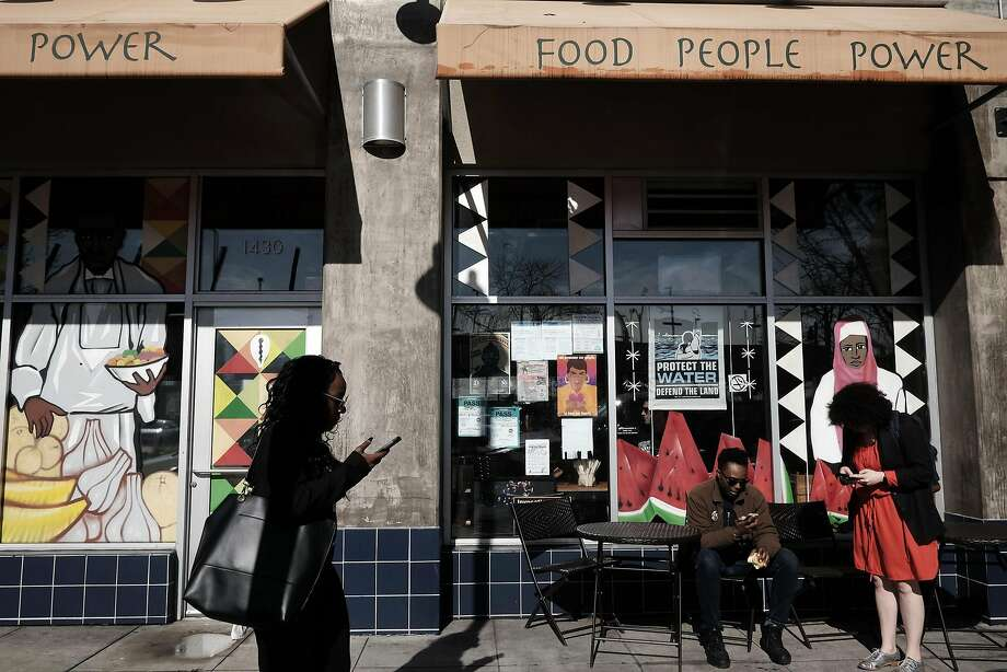 At Mandela Foods Cooperative in Oakland, people sit at tables in the sun. Photo: Michael Short, Special To The Chronicle