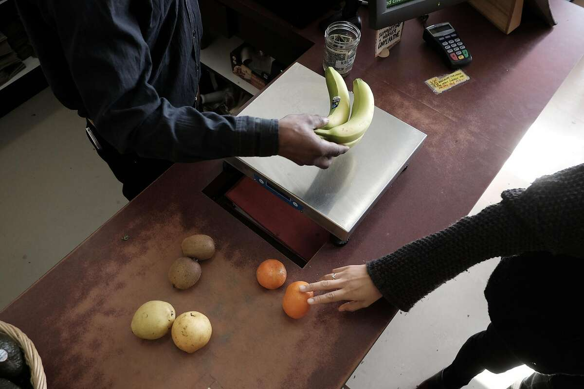 Worker/owner Fekida Wuul weighs out a customers fruit at Mandela Foods Co-op in Oakland, CA on Friday, February 10, 2017.