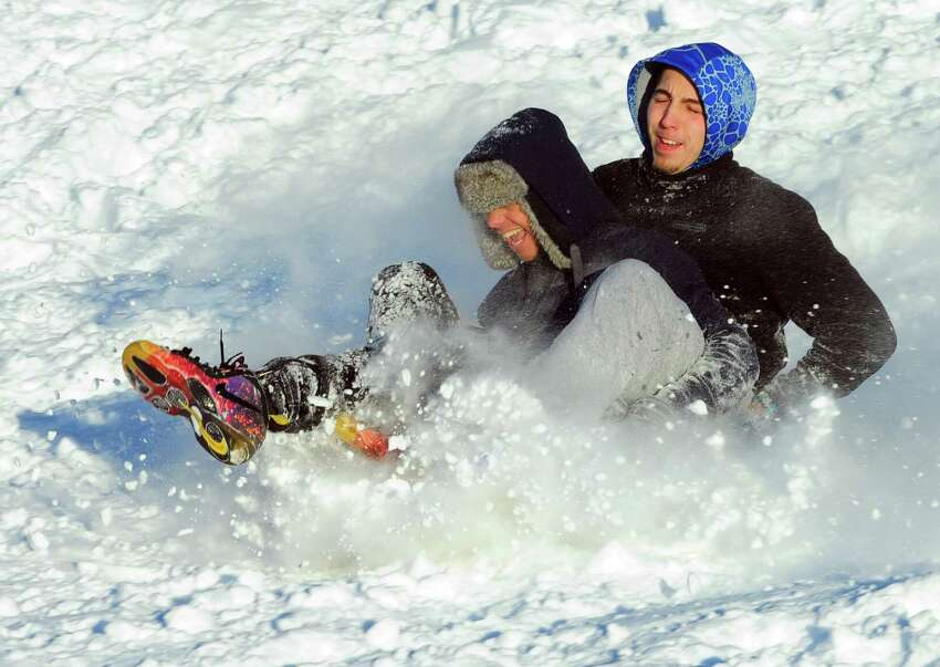 Devon Mero, 15, and his friend Troy Thompson, 16, in back, hit a snow ramp as they sled on the hill at Derby High School in Derby, Conn., on Friday Feb. 10, 2017.