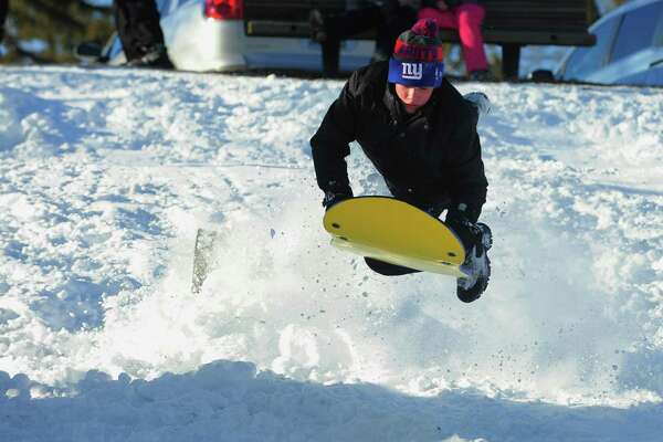 Nick DeManche, 12, flies off a ramp while sledding on the hill at Boothe Memorial Park in Stratford, Conn., on Friday Feb. 10, 2017.