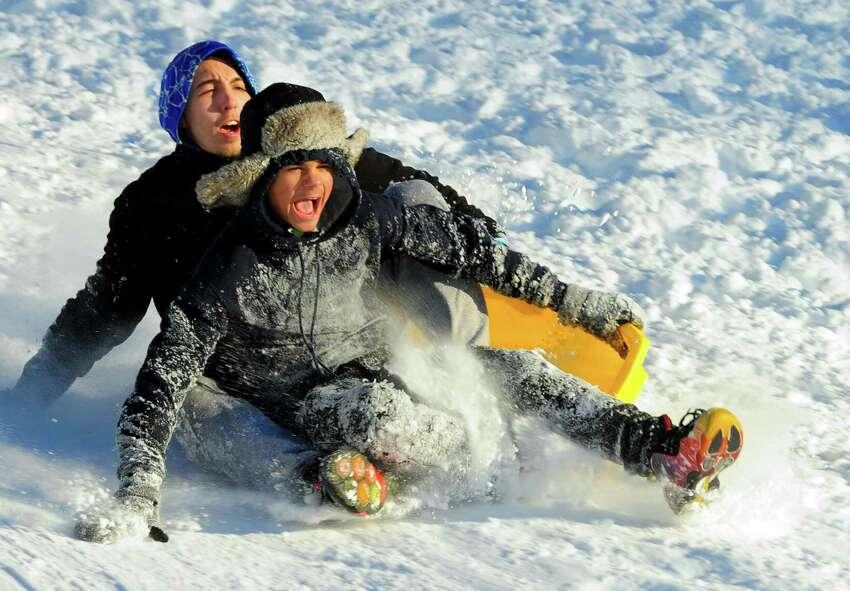 Local kids enjoy sledding down the hill at Derby High School in Derby, Conn., on Friday Feb. 10, 2017.