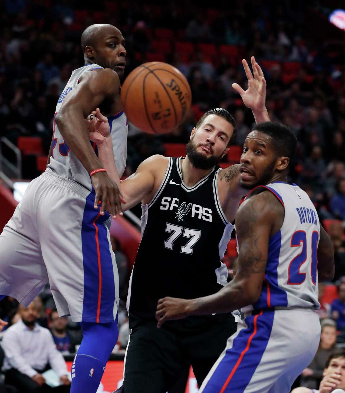 San Antonio Spurs center Joffrey Lauvergne (77) and Detroit Pistons forward Anthony Tolliver, left, and guard Dwight Buycks (20) follow the loose ball during the first half of an NBA basketball game, Saturday, Dec. 30, 2017, in Detroit. (AP Photo/Carlos Osorio)