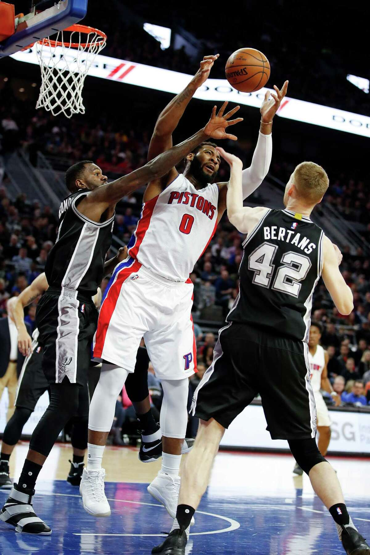 AUBURN HILLS, MI - FEBRUARY 10: Andre Drummond #0 of the Detroit Pistons grabs a first half rebound between Dewayne Dedmon #3 and Davis Bertans #42 of the San Antonio Spurs at the Palace of Auburn Hills on February 10, 2017 in Auburn Hills, Michigan. NOTE TO USER: User expressly acknowledges and agrees that, by downloading and or using this photograph, User is consenting to the terms and conditions of the Getty Images License Agreement.